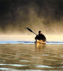 Person kayaking with fog