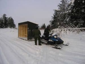 guys pulling and ice shelter with snowmobile